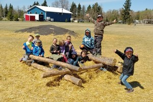 children making a log fort with logs and hay